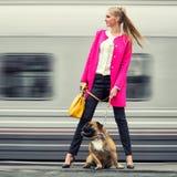 Schönes modernes Mädchen mit einem Hund auf der Plattform lizenzfreie stockfotografie