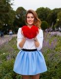 Schönes modernes Mädchen mit rotem Herzen im Park am warmen Sommerabend Lizenzfreie Stockfotos
