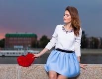 Schönes modernes Mädchen mit rotem Herzen im Park am warmen Sommerabend, der auf einer Steinbank des Flusses allein mit einem Re  Stockfotos