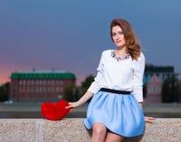 Schönes modernes Mädchen mit rotem Herzen im Park am warmen Sommerabend, der auf einer Steinbank des Flusses sitzt Lizenzfreie Stockbilder