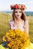 Schönes modernes recht herrliches Mädchen im Kleid auf dem Blumenfeld Nettes Mädchen mit Kranz von Blumen auf ihrem Kopf und Blum Stockbilder
