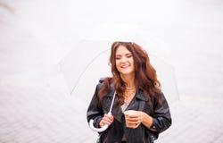 Schönes, modisches, stilvolles Mädchen, das unter transparentem Regenschirm in der Straße sich versteckt Das Trinken nehmen Kaffe stockfotografie