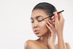 Schönes Mulattemädchen tut hübsches Make-up lizenzfreie stockfotografie