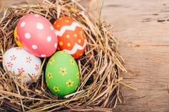 Schönes multi Farbei Ostern im Stroh auf hölzernem lizenzfreie stockbilder