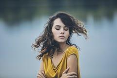 Schönes Nahaufnahmeporträt des jungen Mädchens auf dem Hintergrund des Wassers Lizenzfreie Stockfotos