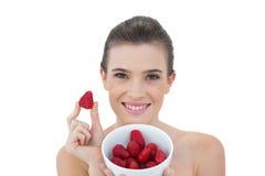 Schönes natürliches braunes behaartes Modell, das eine Schüssel Erdbeeren zeigt Lizenzfreies Stockbild