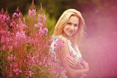 Schönes nettes blondes Mädchen im hellen Kleid ist in den Farben von FI Stockbild