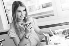 Schönes nettes blondes Trinken der jungen Frau Stockfotos
