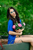 Schönes nettes Brunettemädchen im blauen Kleid mit kreativem blauem Make-up und Blumenstrauß vieler Blumen, Rosen sitzen im Stief Stockfotografie