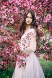 Schönes nettes Brunettemädchen mit dem langen Haar, Braut im transparenten Boudoirkleid der Spitzes, Dekoration, nahe dem Baum bl stockfotografie