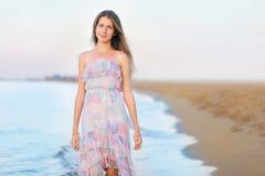 Schönes nettes junges Mädchen auf dem Strand nahe dem Meer Stockbild