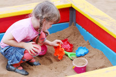 Schönes nettes kleines Mädchen, das im Sandkasten spielt Lizenzfreie Stockfotos