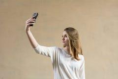 Schönes nettes Mädchen auf einem beige Hintergrund Ohne jedermann Blondes Mädchen mit grünen Augen Sie betrachtet das Telefon Ges Stockbilder