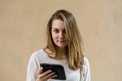 Schönes nettes Mädchen auf einem beige Hintergrund Ohne jedermann Blondes Mädchen mit grünen Augen Sie schaut zur Platte Geschäft Stockfotografie