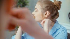 Schönes nettes Mädchen, das mit jemand spricht und zu Hause Hörnchen während des Frühstücks isst stock footage