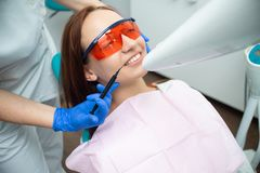 Schönes, nettes Mädchen im Stuhl des Zahnarztes Zahnmedizinische Behandlung Zahnmedizinische Klinik stockbild