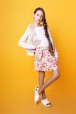 Schönes nettes Modemädchen Jugend in einer Strickjacke und in einem skir auf gelbem Hintergrund mit der langen Haaraufstellung Lizenzfreies Stockfoto