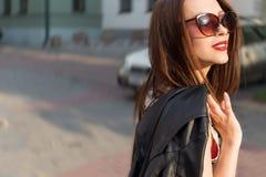Schönes nettes sexy glückliches lächelndes Brunettemädchen in der großen Sonnenbrille gehend um die Stadt bei Sonnenuntergang Stockfotografie