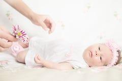 Schönes neugeborenes Mädchen, das eine Blume hält Stockbild
