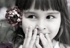 Schönes neugieriges Mädchen mit einer Blume in ihrem Haar Stockfotografie