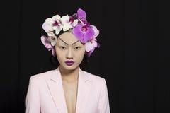 Schönes orientalisches Mädchen mit Orchideen-Blumen stockfotografie