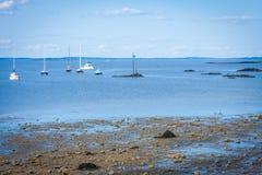 Schönes Ozeanufer mit Booten im Wasser herein stockbild