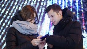 Schönes Paar benutzt mobilen App am schneebedeckten Abend, am Weihnachten und am neuen Jahr stock footage