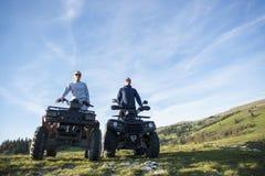 Schönes Paar passt den Sonnenuntergang vom Berg auf, der auf quadbike sitzt stockfoto