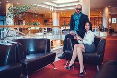 Schönes Paar sitzt in der Halle des Hotels Stockfotografie