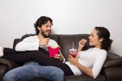 Schönes Paar spricht auf der Couch Essen des Popcorns Relaxi lizenzfreie stockfotografie