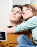 Schönes Paar stellt sich die Zukunft ihres ungeborenen Kindes vor Lizenzfreies Stockfoto