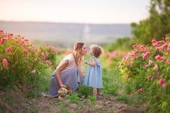 Schönes Paarkindermädchen mit Mutter gehen im Frühjahr Garten mit rosa Blütenrosenblumen, Sonnenuntergangzeit stockbilder