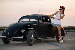 Schönes Pin-up-Girl, das mit heißem Straßenauto aufwirft stockbild