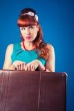 Schönes Pin-up-Girl, das mit Weinlesekoffer gegen Blau aufwirft Stockfoto