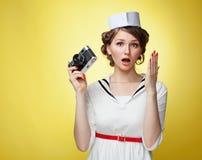 Schönes Pin-up-Girl kleidete einen Seemann, der eine Weinlesekamera und -schreie hinter seiner Hand hält Gelber Hintergrund, Absc Stockfotos