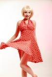 Schönes Pinupmädchen in der blonden Perücke und im Retro- roten Kleidertanzen. Partei. Stockfotografie