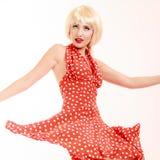 Schönes Pinupmädchen in der blonden Perücke und im Retro- roten Kleidertanzen Party Stockfoto