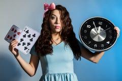 Schönes Pinupmädchen in einem blauen Kleid, das große Uhr auf einem blauen Hintergrund hält Stockfotos