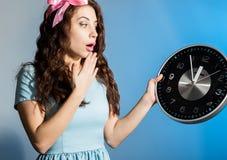 Schönes Pinupmädchen in einem blauen Kleid, das große Uhr auf einem blauen Hintergrund hält Lizenzfreies Stockfoto