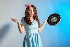 Schönes Pinupmädchen in einem blauen Kleid, das große Uhr auf einem blauen Hintergrund hält Lizenzfreie Stockfotografie
