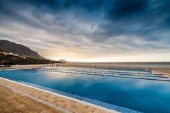 Schönes Pool entlang dem Ozean an der Dämmerung Stockbild