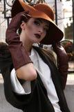 Schönes Porträt der damenhaften Frau im eleganten Mantel und im Hut Stockfotografie