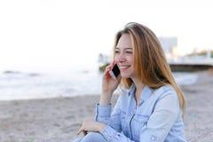 Schönes Porträt der Frau spricht über Mobile mit Lächeln und sitzt Lizenzfreie Stockbilder