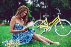 Schönes Porträt der jungen Frau, das ein Buch mit Fahrrad im Park liest stockfotografie