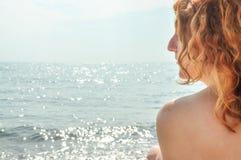 Schönes Porträt in der Profilnahaufnahme einer jungen rothaarigen gelockten Frau durch das Meer auf dem Strand in Italien mit Kop lizenzfreie stockfotos