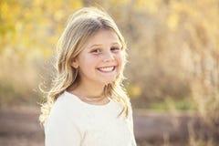 Schönes Porträt des lächelnden kleinen Mädchens draußen Stockbild