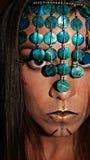 Schönes Porträt einer jungen Frau, welche die Kamera mit einem Gold betrachtet und Braun bildet das Design, das ihr Gesicht mit e stockfoto