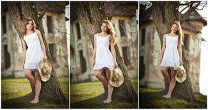 Schönes Porträtmädchen mit Hut nahe einem Baum im Garten. feenhafte Prinzessin im weißen Kleid im Garten. Porträt des ländlichen M Lizenzfreies Stockbild
