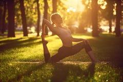 Schönes Praxisyoga asana Königs Pigeon der jungen Frau rajakapotasana Haltung im Park bei Sonnenuntergang Stockfotos