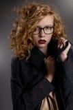 Schönes pussy-haariges Mädchen in einem Mantel und in den Gläsern Lizenzfreie Stockfotos